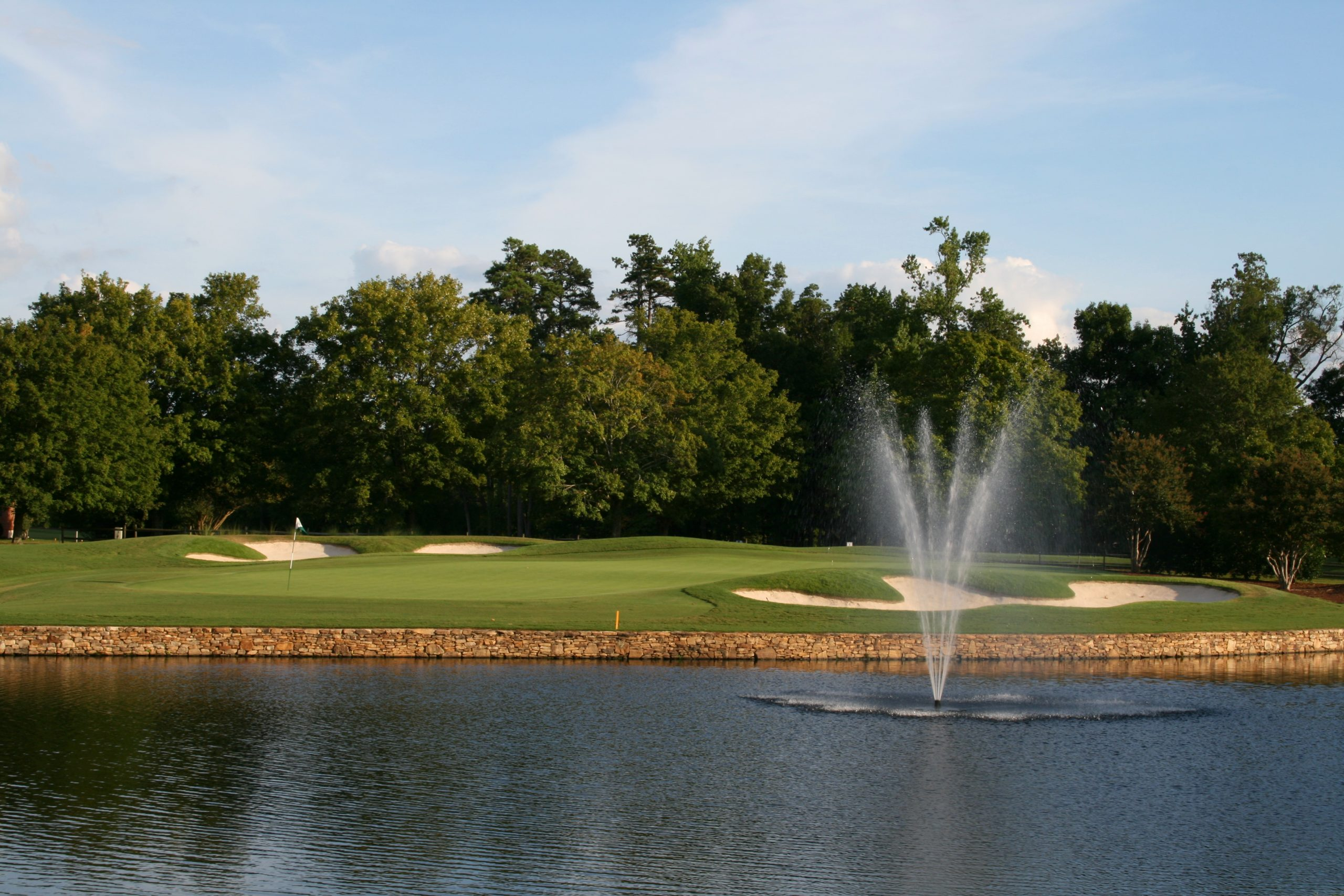 Golf green with sand bunkers, water hazard fountain and trees