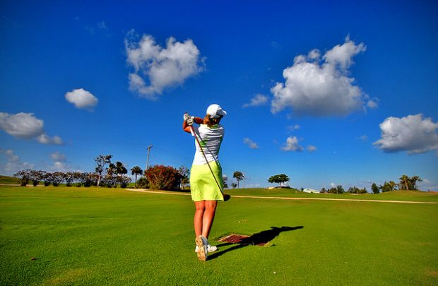 Female golfer on perfect blue sky day